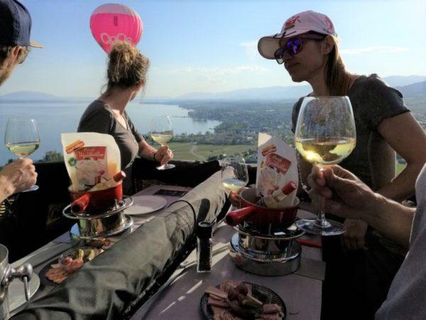 Photo d'une fondue entre amis depuis la nacelle d'un montgolfière Ballons du Léman au dessus du Lac Léman