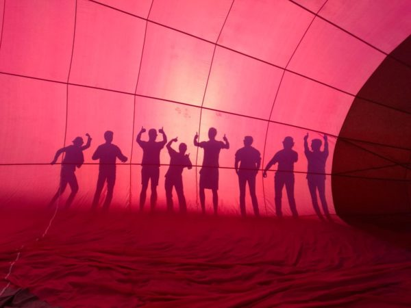 8 personnes derrière le ballon d'une montgolfière