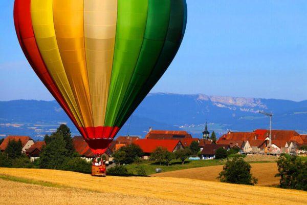 Photo d'une montgolfière Ballons du Léman dans la campagne suisse au moment de l'atterrissage