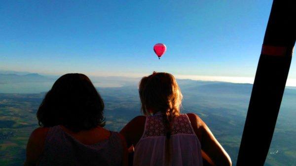 Photo de 2 personnes qui contemplent le paysage Suisse depuis la nacelle d'une montgolfière Ballons du Léman